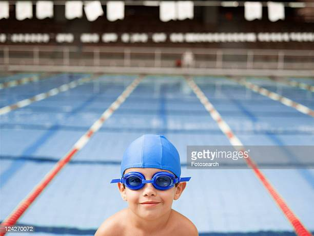 Boy wearing goggles by swimming pool (portrait)