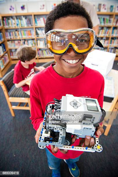 Boy wearing goggles posing with plastic blocks in library