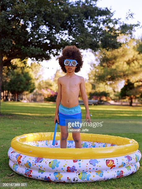 Boy (7-9) wearing goggles, standing in paddling pool