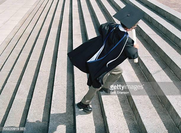 boy (7-9) wearing graduation cap and gown running up steps - wonderkind stockfoto's en -beelden