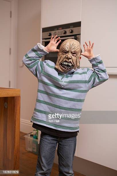 Boy wearing Halloween mask in kitchen