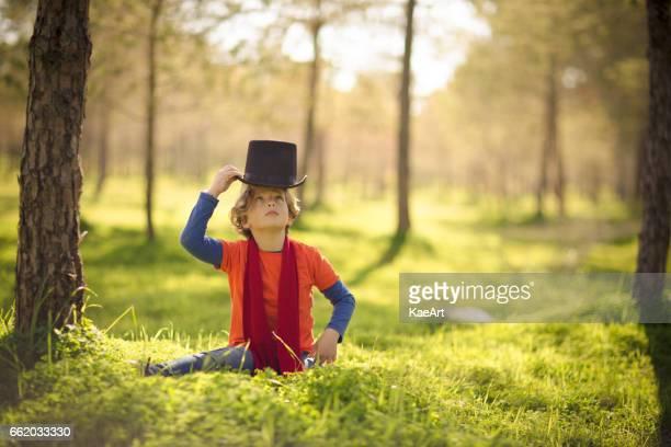 Pojke som bär hatt i en grönskande park