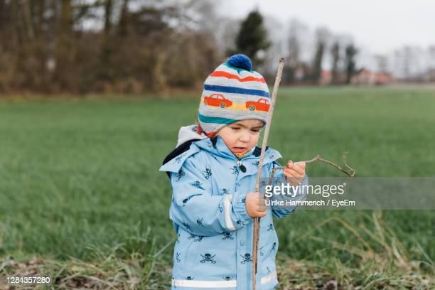 boy wearing hat on field - jacket stock pictures, royalty-free photos & images