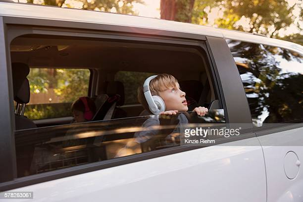 Boy wearing headphones gazing out of car window