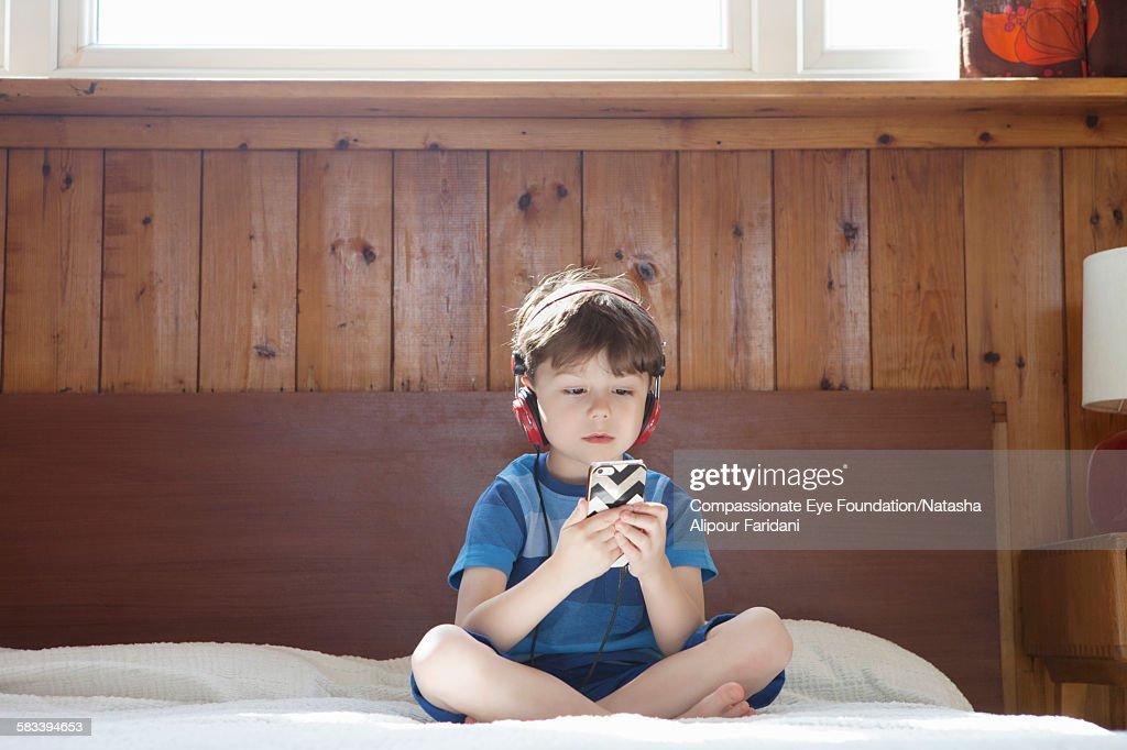 Boy wearing headphones listening to music : Stock Photo