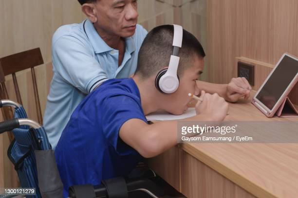 boy wearing headphones looking at digital tablet at home - leaning disability stock pictures, royalty-free photos & images