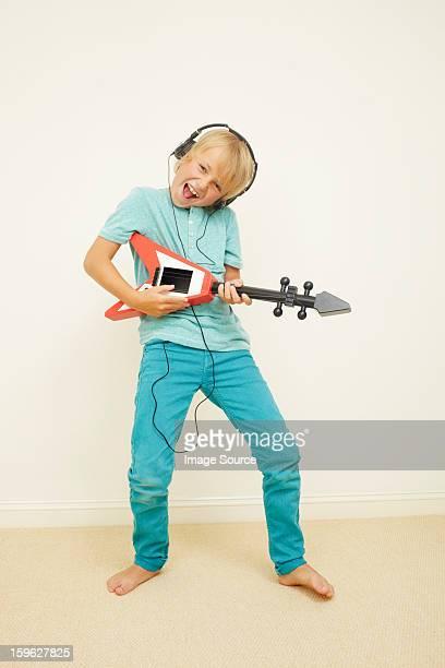 Boy wearing headphones playing guitar