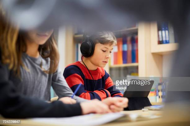 Boy wearing headphones while looking at digital tablet in classroom