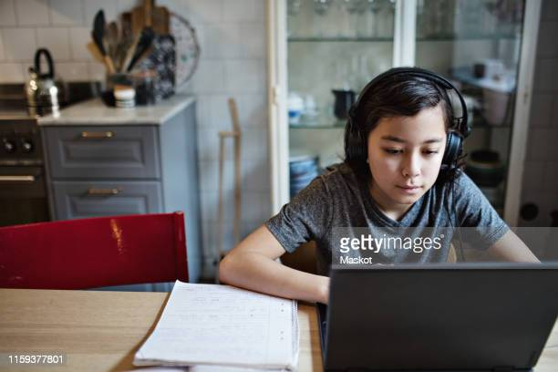 boy wearing headphones while using laptop during homework at home - online class stock pictures, royalty-free photos & images