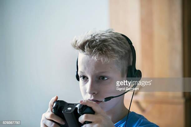 boy wearing headset and playing video game, freiburg im breisgau, baden-w��rttemberg, germany - sigrid gombert fotografías e imágenes de stock