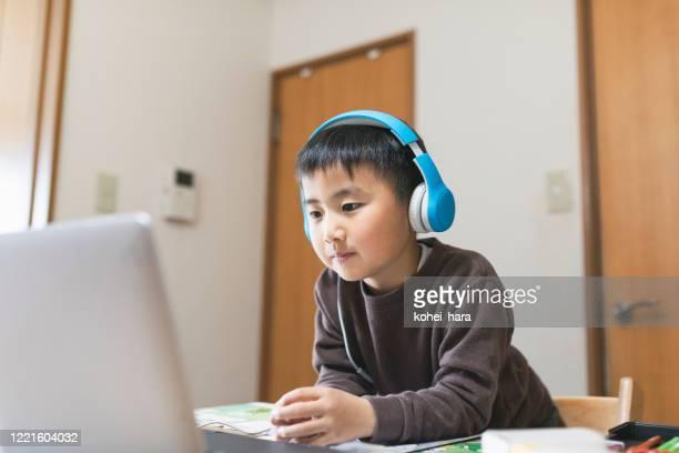 ラップトップでeラーニングコースを受講するヘッドセットを身に着けている少年 - individual event ストックフォトと画像