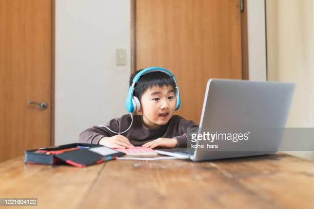ラップトップでeラーニングコースを受講するヘッドセットを身に着けている少年 - %e... ストックフォトと画像