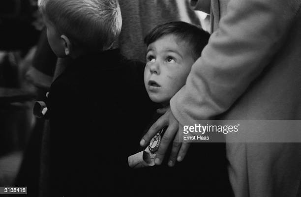 A boy wearing his identification looks up in awe at his surroundings as he arrives at Ellis Island New York 1951 He is one of the passengers on the...