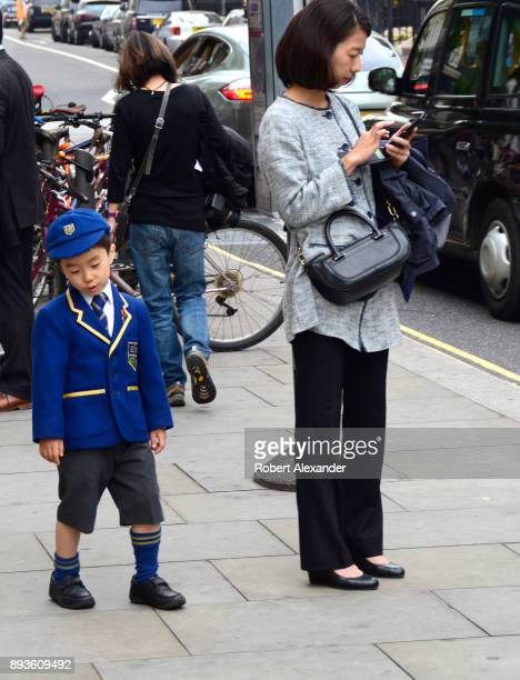 A boy wearing his school uniform stands with his mother as she uses her smartphone in the Belgravia district of London England