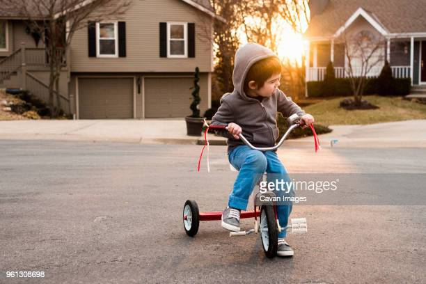 boy wearing hooded jacket while sitting on tricycle - tricycle stock pictures, royalty-free photos & images