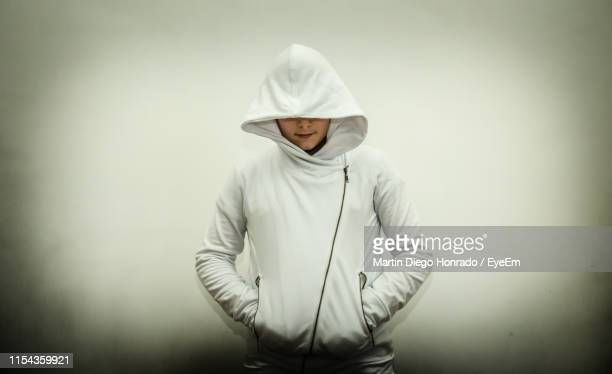 boy wearing hooded shirt while standing against gray background - hooded top stock pictures, royalty-free photos & images
