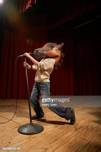 Boy (11-13) wearing horse mask performing on stage, holding microphone