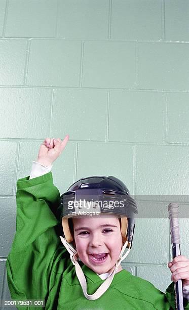 Boy (4-6) wearing ice hockey helmet, arm raised, smiling