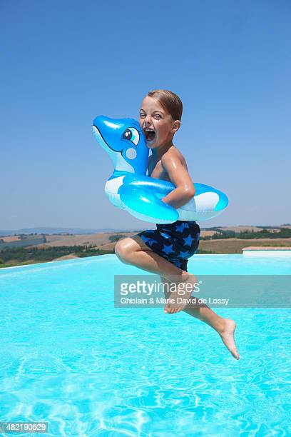 Boy wearing inflatable ring jumping into swimming pool
