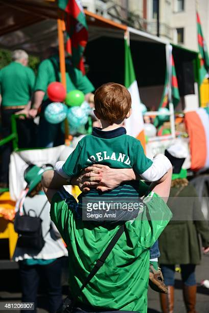 Boy wearing Ireland Tshirt on father's shoulder at the Saint Patrick's Day Parade in London