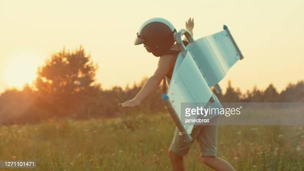 ジェットパックの翼を身に着けている少年が遊ぶ。 - パイロットサングラス ストックフォトと画像