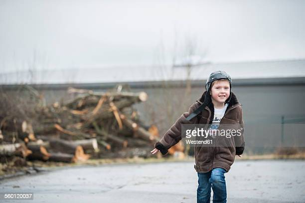 Boy wearing leathet jacket running in backyard