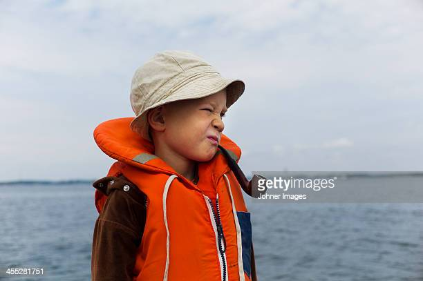Boy wearing life vest with smoking pipe