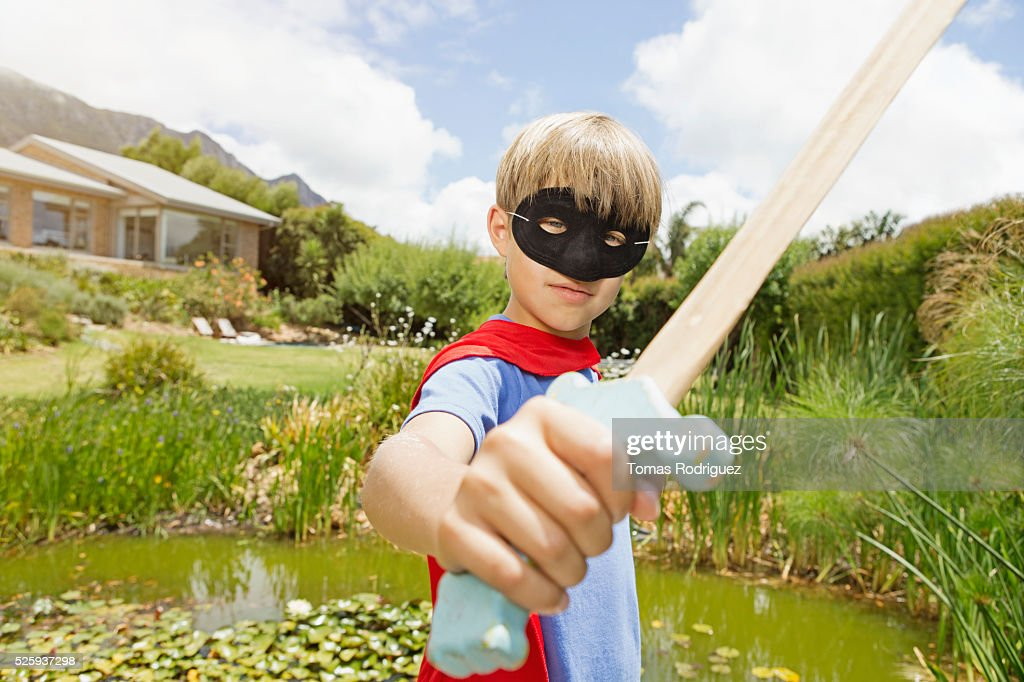 Boy (6-7) wearing mask and holding wooden sword : Stockfoto