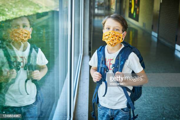 boy wearing mask in school mirrored in window - schoolboy stock pictures, royalty-free photos & images