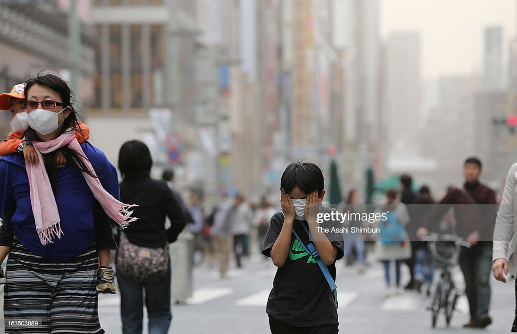 A boy wearing mask protects his face from dusty wind as haze covers Tokyo on March 10, 2013 in Tokyo, Japan. Strong Northern wild by the cold front blow up dust and cover Japan's capital.