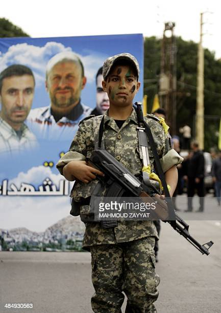 A boy wearing military fatigue and holding an AK47 poses for a picture during the funeral of AlManar cameraman Mohammad Mantash who was killed in...