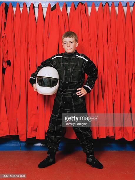 Boy (9-11) wearing motor racing gear, helmet under arm, portrait