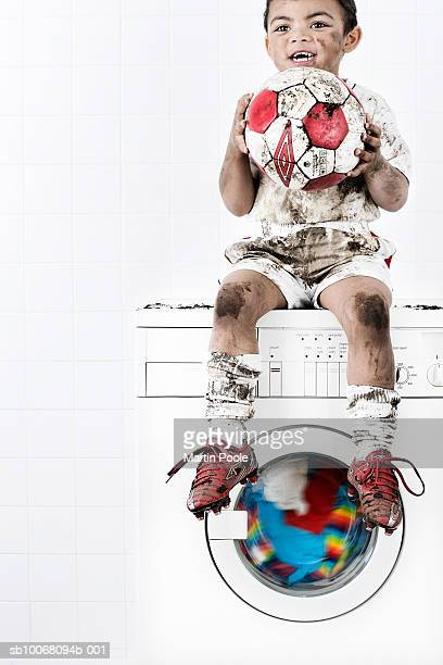 Boy (2-3) wearing muddy soccer kit, sitting on washing machine