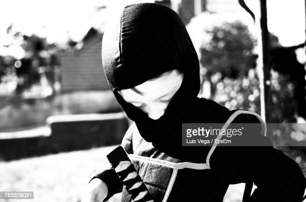 Boy Wearing Ninja Costume While Standing Outdoors