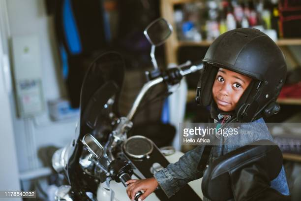 Boy wearing open face helmet sitting on motorcycle