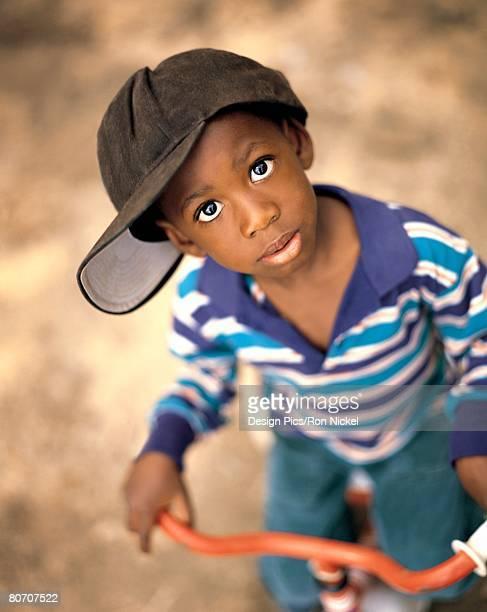 Boy wearing over sized hat riding bike