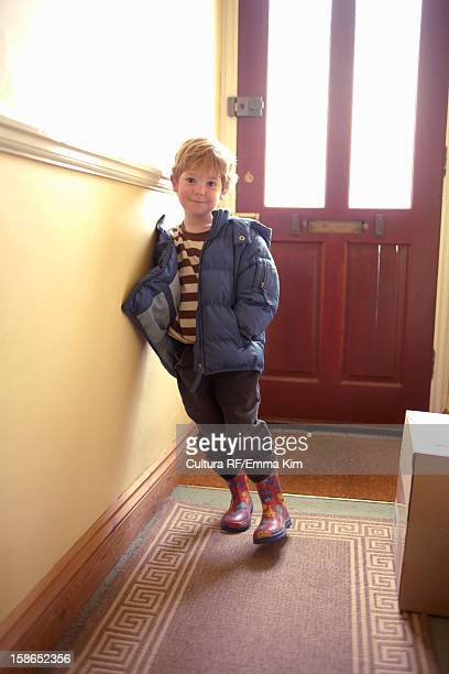 Boy wearing parka and boots indoors