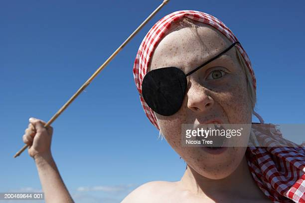 Boy (7-9) wearing pirate costume, waving stick, outdoors, portrait