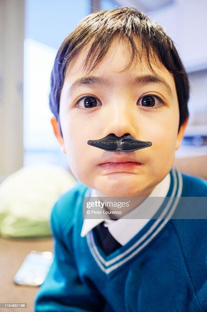 Boy wearing plastic moustache : Stock Photo