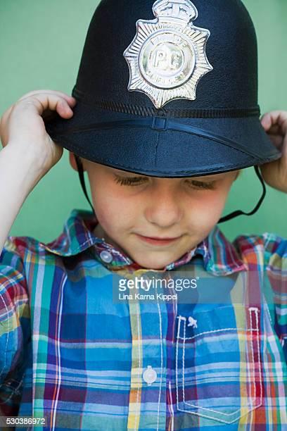 Boy wearing police helmet