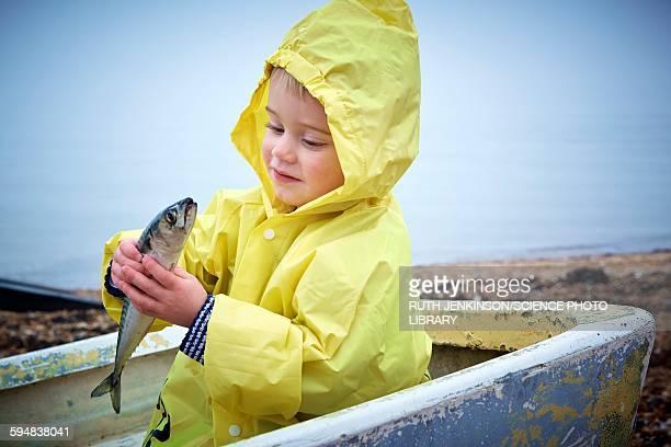 Boy wearing raincoat holding a mackerel