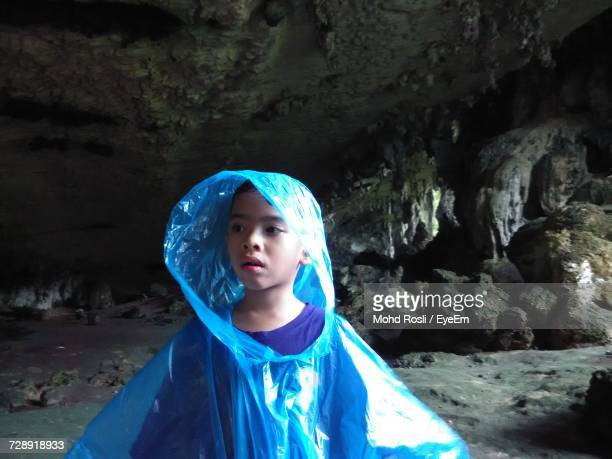 Boy Wearing Raincoat In Cave At Niah National Park