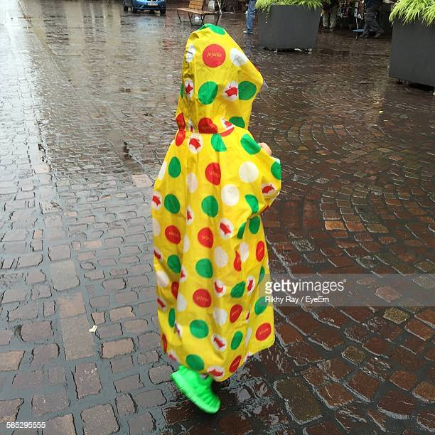 Boy Wearing Raincoat Standing On Cobblestone Street During Rainy Day