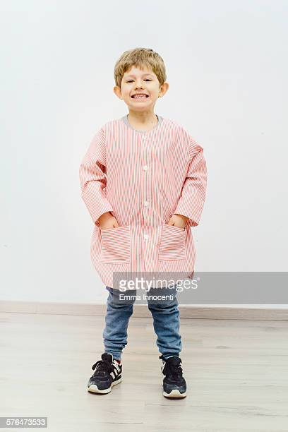 boy wearing red nursery school apron - hands in pockets stock photos and pictures