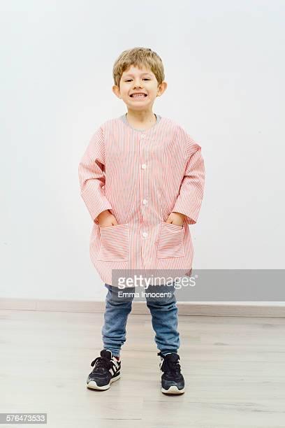 boy wearing red nursery school apron