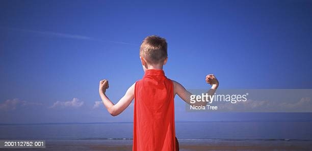 boy (5-7) wearing red superhero cape flexing muscles, rear view - superhero stock pictures, royalty-free photos & images