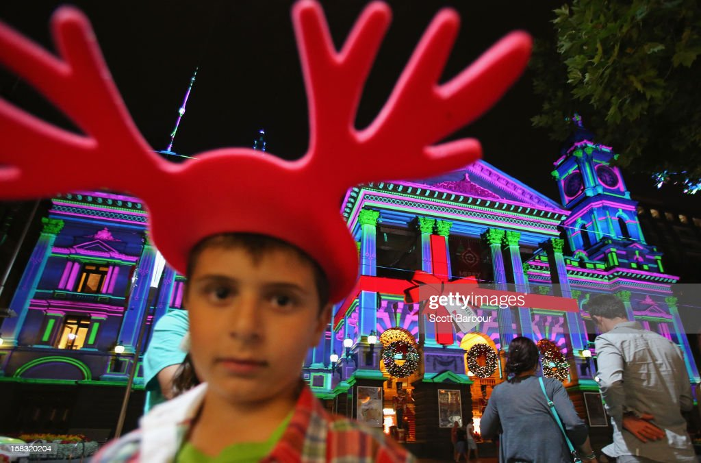 A boy wearing reindeer antlers looks on as Melbourne Town Hall is illuminated with Christmas projections as Melbourne lights up for Christmas on December 13, 2012 in Melbourne, Australia.