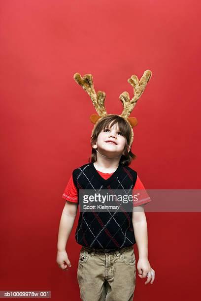 Boy (4-5) wearing reindeer antlers, on red background
