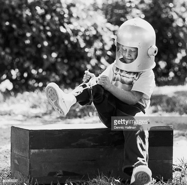 Boy wearing retro space helmet tying his shoe