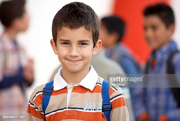 Boy (8-10) wearing rucksack, smiling, portrait, close-up